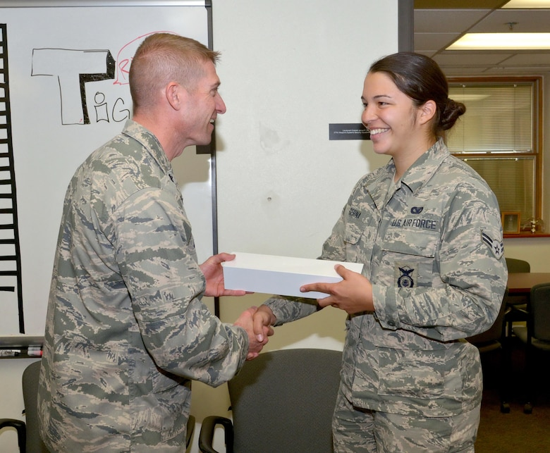 Lt. Col. James Meier, 377th Weapons System Security Squadron commander, presents an Apple iWatch to Airman 1st Class Alejandra Serna. Serna won the prize for her participation in the 37th Training Wing's 2016 Innovation Day. Of about 1,200 Airmen in that wing, she was the only one to visit every demonstrated showcase. (Photo by Jamie Burnett)