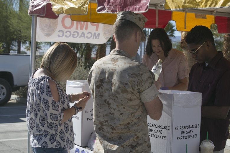 Members of the Provost Marshal's Office help a Marine Corps Air Ground Combat Center patron peel off medication labels during the PMO Drug Take Back at Heritage Park, Oct. 22, 2016. The take back is held to give the Combat Center community the opportunity to anonymously turn in any expired or unneeded prescription drugs for proper disposal.  (Official Marine Corps photo by Cpl. Thomas Mudd/Released)