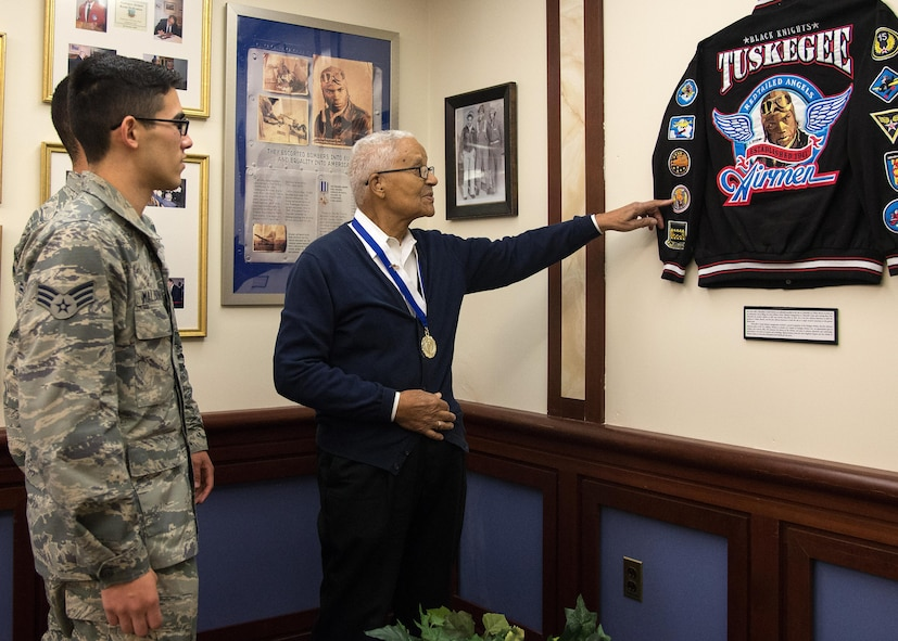 Retired Col. Charles E. McGee, an original Tuskegee Airman, points to patches on a Tuskegee Airmen jacket that is displayed at the Minuteman Commons on base Oct. 27, while Senior Airman Alfredo Maldonado, right, and Airman 1st Class Quinton Coke, both personnelist with the 66th Force Support Squadron, look on. McGee met with Airmen and discussed Air Force history and challenged each Airmen to believe in themselves. (U.S. Air Force photo by Mark Herlihy)