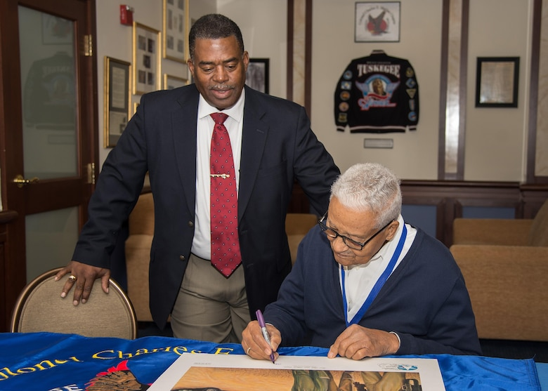 Retired Col. Charles E. McGee, an original Tuskegee Airman, signs a lithograph during a visit to the Minuteman Commons Oct. 27, while Galen Williams, the local Col. Charles E. McGee Tuskegee Airmen Chapter president, looks on. McGee held an impromptu meeting this week with Airmen prior to speaking at an event in Boston co-hosted by the New England Tuskegee Airmen Chapter and the local chapter bearing his name.
