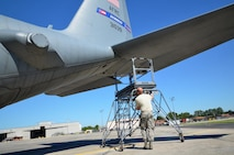 Staff Sgt. John McDermott, 94th Maintenance Squadron avionics instruments and flight control, moves a maintenance ladder used to reach C-130 engines on the flight line at Dobbins Air Reserve Base on September 28, 2016. Maintenance members sometimes shade their eyes from the sun during a clear day. (U.S. Air Force photo by Senior Airman Lauren Douglas)