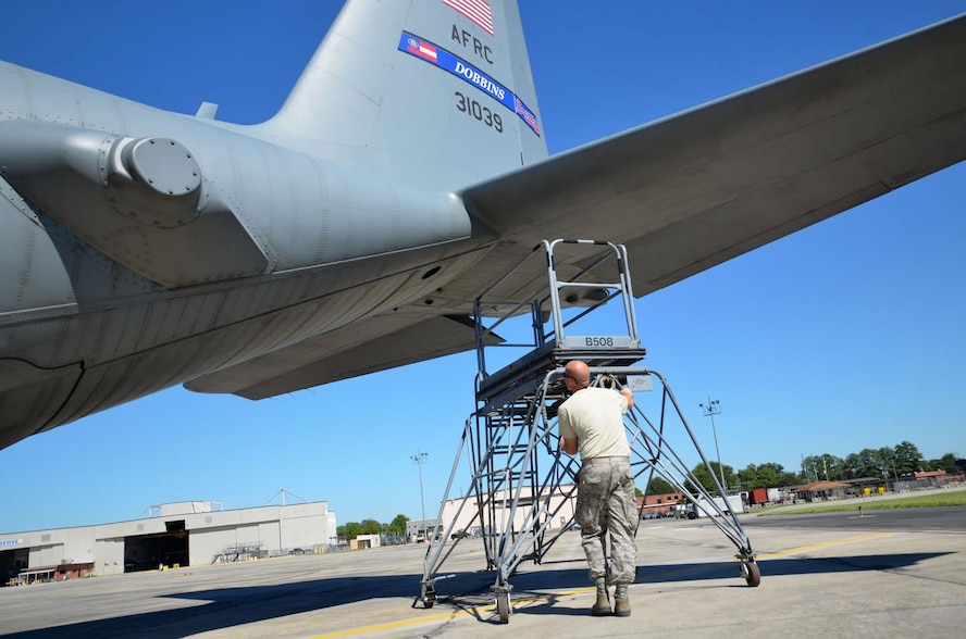 Staff Sgt. John McDermott, 94th Maintenance Squadron avionics instruments and flight control, moves a maintenance ladder used to reach C-130 engines at Dobbins Air Reserve Base on September 28, 2016. Maintenance members sometimes shade their eyes from the sun during a clear day. (U.S. Air Force photo by Senior Airman Lauren Douglas)