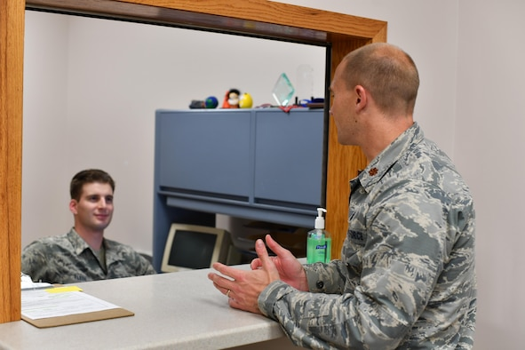 SrA Joshua Fleek, 319th Medical Group x-ray technologist, and Maj. Corby Heyne, 319th Medical Group medical information systems and resources flight commander, converse Oct. 26, 2016, in the Medical Treatment Facility on Grand Forks Air Force Base, N.D. Heyne is leading the Patient and Family Engagement initiative at Grand Forks AFB to provide higher quality service to patients. (U.S. Air Force photo by Airman 1st Class Elijaih Tiggs)