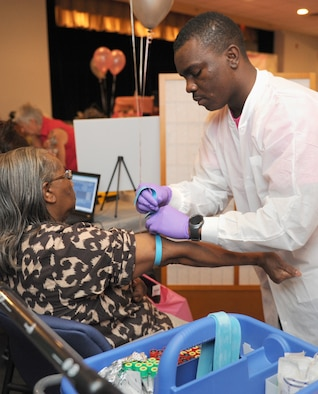 Mamie Chatman, spouse of retired Chief Master Sgt. Roscoe Chatman, prepares to have her blood drawn by Airman 1st Class Isaiah Jones, 81st Diagnostic and Therapeutics Squadron lab technician, during the 5th Annual Mammothon Cancer Screening and Preventative Health Fair at the Don Wylie Auditorium Oct. 28, 2016, on Keesler Air Force Base, Miss. The walk-in event included screenings for multiple types of cancer and chronic diseases in honor of Breast Cancer Awareness Month. Flu shots were also provided upon request. (U.S. Air Force photo by Kemberly Groue/Released)