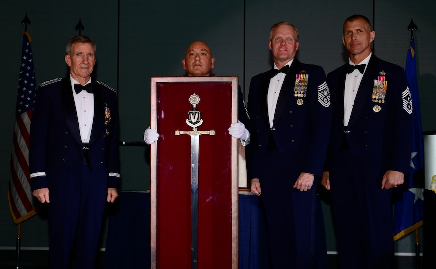 Gen. Hawk Carlisle, commander of Air Combat Command, left, is presented with an Order of the Sword shadowbox by Chief Master Sgt. Jose A. Baraza, 12th Air Force command chief, Davis-Monthan Air Force Base, Ariz., Chief Master Sgt. of the Air Force James Cody and Chief Master Sgt. Steve K. McDonald, ACC command chief, during an Order of the Sword Ceremony at the Hampton Roads Convention Center in Hampton, Va., Oct. 27, 2016. Carlisle, who has commanded ACC since October 2014, is the eighth ACC leader to be inducted into the command's Order of the Sword. (U.S. Air Force photo by Airman 1st Class Kaylee Dubois)