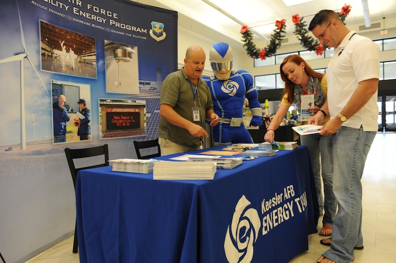 Bruce Groves, Base Operations Support installation energy manager, provides Energy Action Month information to U.S. Navy Lt. Ted Packowski, 22nd Naval Construction Regiment Europe/Africa Action officer, Naval Construction Battalion Center, Gulfport, Miss., and his wife, Sarah, at the base exchange Oct. 28, 2016, on Keesler Air Force Base, Miss. The goals of Energy Action Month are to increase awareness about energy consumption and to encourage energy-saving actions in Airmen, civilians and their families. (U.S. Air Force photo by Kemberly Groue/Released)