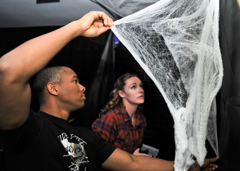 Airman 1st Class Gregory Smith, an avionics technician, and Senior Airman Amber Burns, a non-destructive inspection expert, both assigned to the 28th Maintenance Squadron, hang up decorations for Haunted Camp Lancer on Oct. 27, 2016. Haunted Camp Lancer will be available to all military, dependents and DOD civilians Oct. 28 and 29 from 6-9 p.m. The event is free for all guests, but canned goods or winter clothing donations are encouraged and will be given to the local community. (U.S. Air Force photo by Airman 1st Class Randahl J. Jenson)