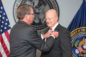 Defense Secretary Ash Cater presents James R. Clapper, the director of the Office of National Intelligence, with the Defense Distinguished Civilian Service Medal at a ceremony at the office's headquarters in Tysons Corner, Va., Oct. 28, 2016. Office of the Director of National Intelligence photo