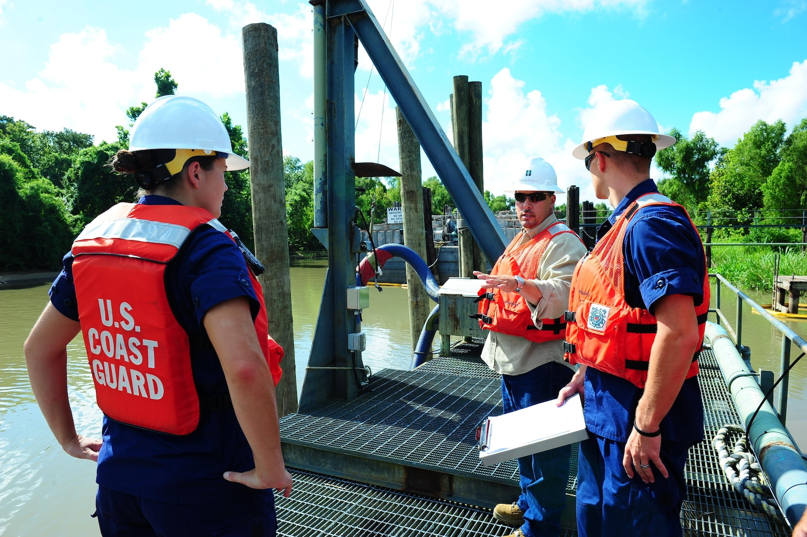 Coast Guard petty officers communicate an environmental health and safety coordinator during a facility inspection. Coast Guard facility inspectors inspect the hoses that transfer oil in order to prevent environmental pollution. (U.S. Coast Guard photo by Petty Officer 3rd Class Carlos Vega)