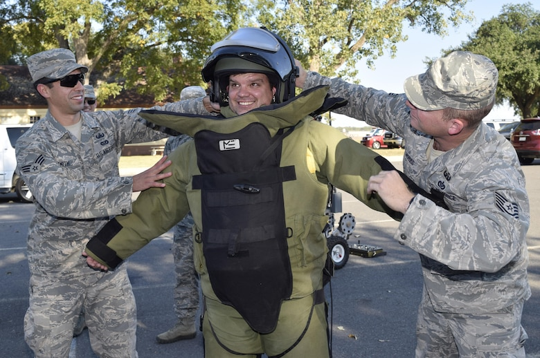 Senior Airman J. Michael Smith left, and Tech. Sgt. Paul Works, right, both with the 2nd Civil Engineer Squadron Explosive Ordnance Disposal flight, secure Matthew Haby of Haby Reality into an EOD 9 bomb suit Oct. 27, 2016 at Barksdale Air Force Base,  Louisiana. The demonstration was part of a civic leader tour sponsored by the 433rd Airlift Wing and hosted by the 307th Bomb Wing. (U.S. Air Force photo by Tech. Sgt. Lindsey Maurice)