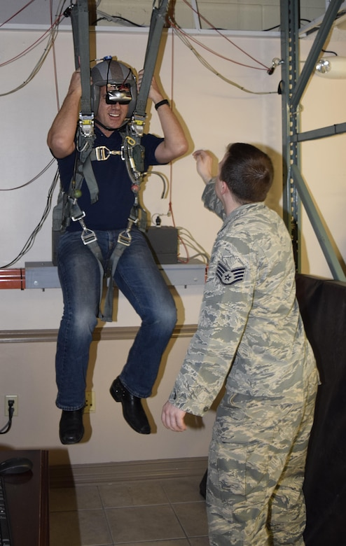 Staff Sgt. Travis Tidwell, 2nd Operations Support Squadron aircrew flight equipment technician, directs Bjorn Dyhdahl, Bjorn's Audio Video president, on what to do during a parachute simulator demonstration Oct. 28, 2016 at Barksdale Air Force Base, Texas. The demonstration was part of a civic leader tour sponsored by the 433rd Airlift Wing and hosted by the 307th Bomb Wing. (U.S. Air Force photo by Tech. Sgt. Lindsey Maurice)