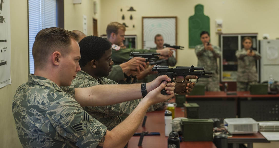 Members of a combat arms instruction class practice proper weapon procedures with M9 Berettas prior to range qualifying at the firing range on Kadena Air Base, Japan, Oct. 25, 2016. Combat arms instructors qualify military members on different weapons prior to events such as deployment. (U.S. Air Force photo by Airman 1st Class Nick Emerick)