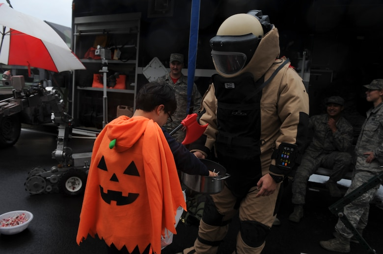 Senior Airman Steven James, 8th Civil Engineering Squadron explosive ordinance disposal technician, hands out candy to children from Sinsido elementary school at Kunsan Air Base, Republic of Korea, Oct. 28, 2016. The children participated in a base tour that included a trick-or-treat Halloween event. (U.S. Air Force photo by Senior Airman Michael Hunsaker/Released)