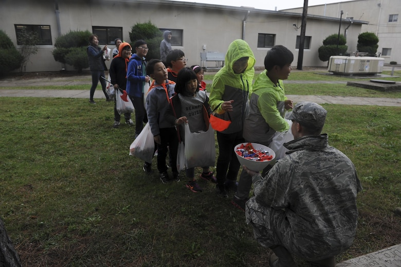 Maj. John Marshall, 8th Civil Engineering engineering flight commander, hands out candy to children from Sinsido elementary school at Kunsan Air Base, Republic of Korea, Oct. 28, 2016. The children participated in a base tour that included a trick-or-treat Halloween event. (U.S. Air Force photo by Senior Airman Michael Hunsaker/Released)
