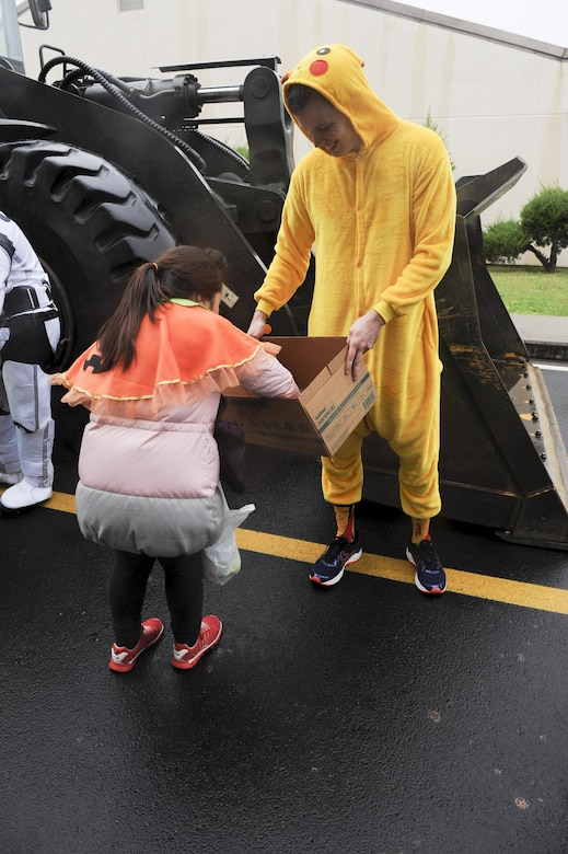 Staff Sgt. Justin Prince, 8th Comptroller Squadron special actions noncommissioned officer, hands out candy to children from Sinsido elementary school at Kunsan Air Base, Republic of Korea, Oct. 28, 2016. The children participated in a base tour that included a trick-or-treat Halloween event. (U.S. Air Force photo by Senior Airman Michael Hunsaker/Released)