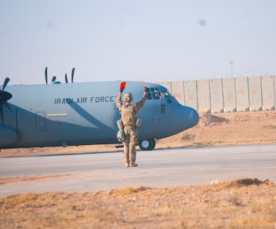 A U.S. Air Force Airman with the 821st Crisis Response Group, signals a taxing Iraqi air force C-130J Super Hercules at Qayyarah West Airfield, Iraq, Oct. 30, 2016. This was the first time a fixed wing aircraft from Iraqi security forces landed at Qayyarah West Airfield since the base was occupied by Islamic State of Iraq and the Levant in 2014. Coalition forces reconstructed the airfield as part of their effort to assist the Iraqi security forces as the seize territory from ISIL. Qayyarah West Airfield serves as a logistics hub for ongoing operations in northern Iraq. (U.S. Army photo by 1st Lt. Daniel Johnson)