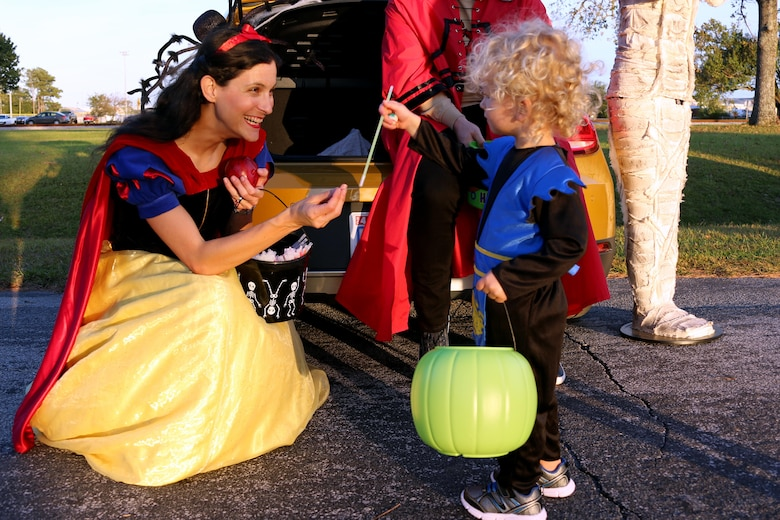 Maj. Janine Garner, left, gives Elias, 2, a candy straw during a Trunk or Treat event aboard Marine Corps Air Station Cherry Point, N.C., Oct. 27, 2016. Marine Corps Community Services hosted the Halloween-inspired event that included face painting; touch the truck displays; and a family glow dance party. Decorated trunks were judged and the highest-rated contestants received door prizes. Garner is the commanding officer for Personal Support Detachment 14, Marine Aircraft Group 14. (U.S. Marine Corps photo by Cpl. Jason Jimenez/Released)