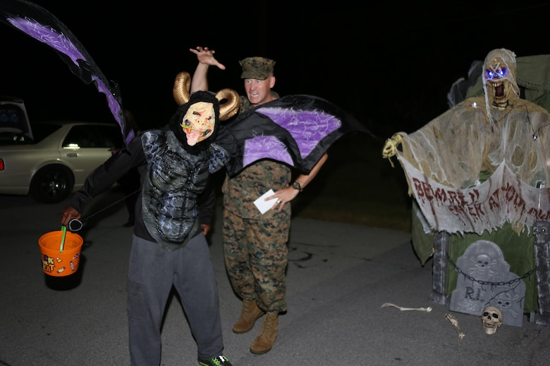 A costumed participant, left, poses in front of Col. Todd Ferry during a Trunk or Treat event aboard Marine Corps Air Station Cherry Point, N.C., Oct. 27, 2016. Marine Corps Community Services hosted the Halloween-inspired event that included face painting; touch the truck displays; and a family glow dance party. Decorated trunks were judged and the highest-rated contestants received door prizes. Ferry is the commanding officer of MCAS Cherry Point. (U.S. Marine Corps photo by Cpl. Jason Jimenez/Released)