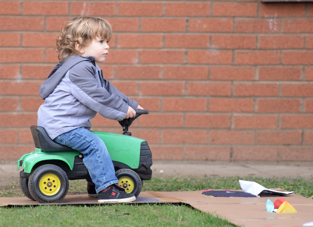 A child plays with a toy tractor during a Fall Festival Oct. 28, 2016, at the child development center on RAF Mildenhall, England. Children and parents took part in a parade then played games and visited a pumpkin patch. (U.S. Air Force photo by Gina Randall)
