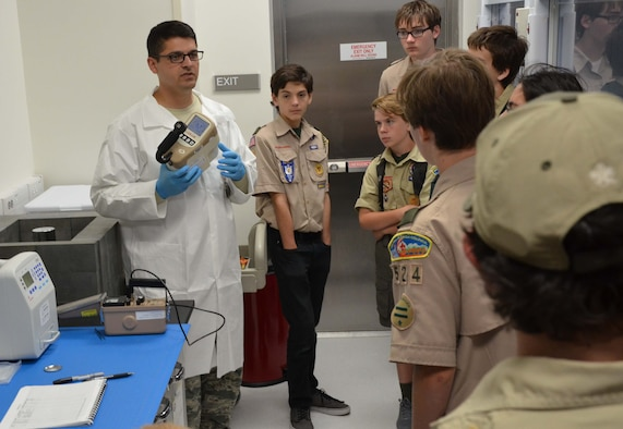 Staff Sgt. Leland La Kemper, a radiochemistry lab technician with the Air Force Technical Applications Center, displays an ion chamber to a group of Boy Scouts who visited AFTAC Oct. 22 to earn their Nuclear Science Merit Badge.  La Kemper explained the importance of 'as low as reasonably achievable' – better known as ALARA -- safety measures to the scouts during their tour of AFTAC's Ciambrone Radiochemistry Lab at Patrick AFB, Fla.  (U.S. Air Force photo by Susan A. Romano)
