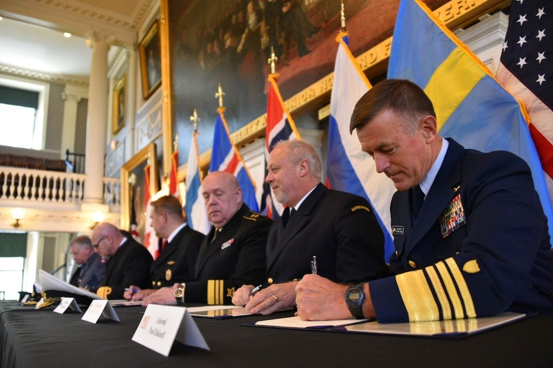 Coast Guard Commandant Adm. Paul Zukunft (right) and the heads of seven other Arctic nations' coast guards sign a joint statement that establishes the frameworks that detail the development of a multi-year strategic plan, avenues to share information, highlight best practices, identify training exercises, and on-the-water combined operations to achieve safe, secure and environmentally-responsible maritime activity in the Arctic in Faneuil Hall in Boston, June 10, 2016. (U.S. Coast Guard photo by Petty Officer 2nd Class Patrick Kelley)