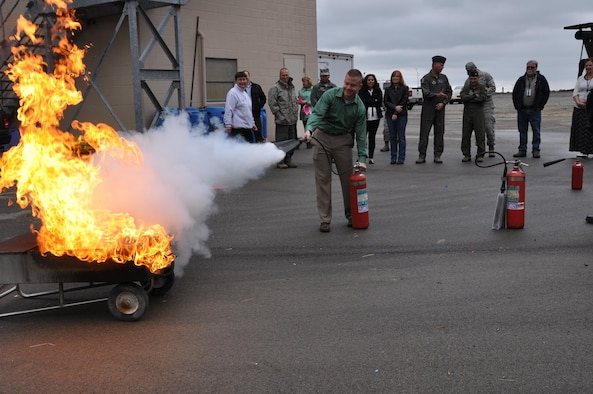 Chadwick McIntosh from the 910th Financial Management office uses a fire extinguisher on a controlled fire during fire safety training Oct. 13, 2016, here. Fire safety training is an annual requirement for members of Youngstown Air Reserve Station. (U.S. Air Force photo/Maj. Polly Orcutt)