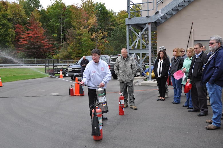 Fran Taylor, 910th Civil Engineer Squadron Fire Department assistant chief of fire prevention, demonstrates a fire extinguisher for members of the 910 Airlift Wing during fire safety training Oct. 13, 2016 here. (U.S. Air Force photo/Maj. Polly Orcutt)