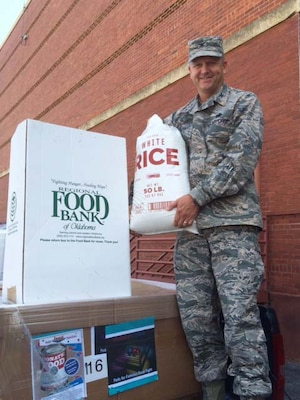 "Air Force Col.  Ken Ruthardt, Defense Logistics Agency Aviation commander at Oklahoma City, drops off rice at the Regional Food Bank of Oklahoma donation box on Tinker Air Force Base, Oklahoma in support of the Feds Feed Families Program, which runs annually from June through August.  Both DLA Aviation and DLA Distribution supported Feds Feed Families this year by challenging each other to a ""food fight"" to see who could donate the most food to the program."