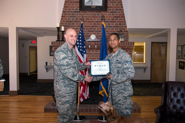 Senior Airman Randle Williams, 23d Security Forces Squadron Military Working Dog handler, accepts MWD Dini's Meritorious Service Award from Maj. Charles Tenney, 23d SFS commander, during a retirement ceremony, Oct. 28, 2016, at Moody Air Force Base, Ga. Dini, an explosive detector dog, served at Moody since April 2009. (U.S. Air Force photo by Airman 1st Class Greg Nash)