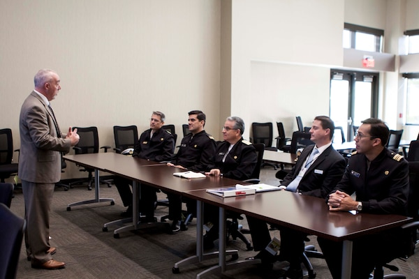 Jim McCormack, deputy director of DLA Distribution's Business Development directorate, discusses DLA Distribution's core capabilities with members of the Chilean Navy on October 28.
