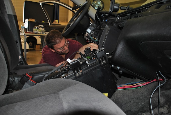 A mechanic with the 502nd Logistics Readiness Squadron at Joint Base San Antonio-Fort Sam Houston installs one of the idle-reduction systems being tested on security forces vehicles. (U.S. Air Force photo by Carole Chiles Fuller)