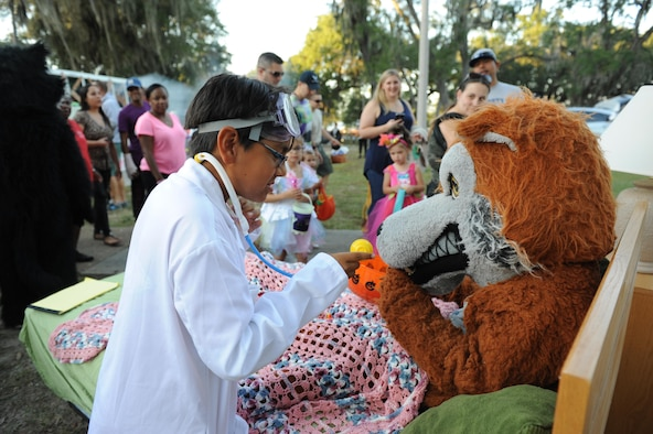 "Carlos Hurtado Jr., son of retired Master Sgt. Carlos Hurtado Sr., portrays a doctor as he checks the vital signs of the 336th Training Squadron red wolf mascot during Ghouls in the Park at Marina Park Oct. 28, 2016, on Keesler Air Force Base, Miss. Ghouls in the Park featured a zombie bus, a haunted house, ""Trunk or Treat"" and games for children of all ages. (U.S. Air Force photo by Kemberly Groue/Released)"