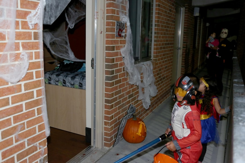 Miguel, 6, left, leads his family into a Halloween-themed barracks room during a Haunted Barracks event aboard Marine Corps Air Station Cherry Point, N.C., Oct. 28, 2016. Marine Wing Headquarters Squadron 2 hosted the event to give Marines living in the barracks an opportunity to celebrate Halloween with other MWHS-2 Marines and their families. Children went door-to-door with their parents and received candy from the Marines.
