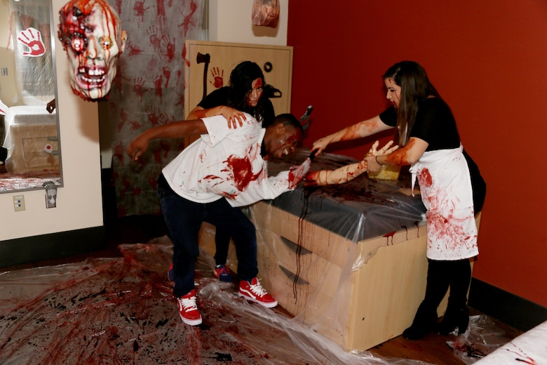 Lance Cpl. Jailene Burciaga, left, Pfc. Deandre Guilford, center, and Pfc. Hannah Mainz re-enact their butcher shop demonstration during a Haunted Barracks event aboard Marine Corps Air Station Cherry Point, N.C., Oct. 28, 2016. Marine Wing Headquarters Squadron 2 hosted the event to give Marines living in the barracks an opportunity to celebrate Halloween with other MWHS-2 Marines and their families. Children went door-to-door with their parents and received candy from the Marines. Guilford is an administrative specialist; Burciaga and Mainz are embarkation specialists, all with MWHS-2.