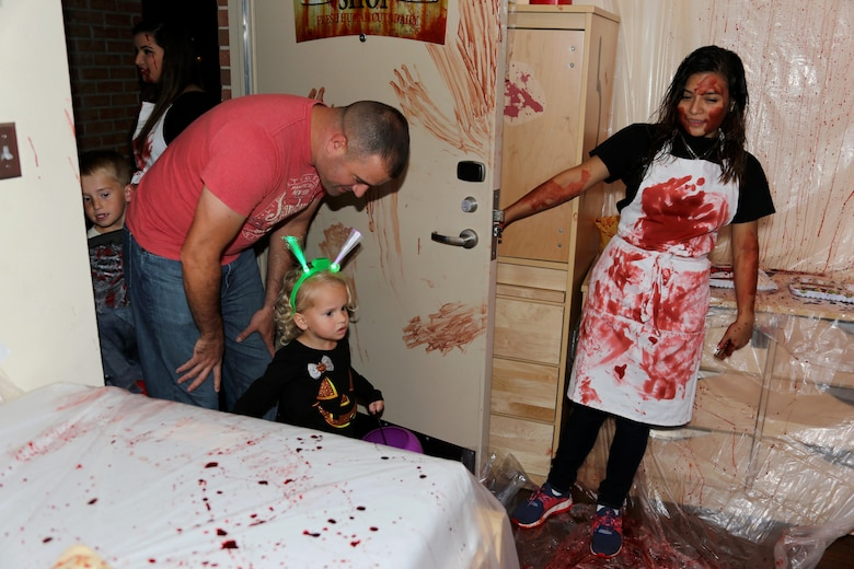 Abby, 2, center, is let into a butcher shop-themed room by Lance Cpl. Jailene Burciaga during a Haunted Barracks event aboard Marine Corps Air Station Cherry Point, N.C., Oct. 28, 2016. Marine Wing Headquarters Squadron 2 hosted the event to give Marines living in the barracks an opportunity to celebrate Halloween with other MWHS-2 Marines and their families. Children went door-to-door with their parents and received candy from the Marines. Burciaga is an embarkation specialist with MWHS-2.