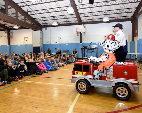 Sparky, the official firefighter mascot smiles for the camera as Niagara Falls Air Reserve Station Assistant Fire Chief Joe Foucha talk to children of Colonial Village School, Niagara Falls, N.Y. on October 13, 2016. Air Base fire fighters were on hand to speak to children and teachers about fire safety during Fire Prevention week. (U.S. Air Force photo by Peter Borys)