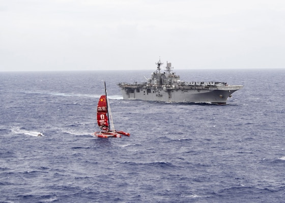 """ Sailors aboard a rigid-hull inflatable boat, launched from the amphibious assault ship USS Makin Island (LHD 8), approach the trimaran of a missing Chinese mariner during a search and rescue mission in the western Pacific Ocean. The Makin Island Amphibious Ready Group is deployed with the embarked 11th Marine Expeditionary Unit in support of the Navy™s maritime strategy in the U.S. 3rd Fleet area of responsibility."