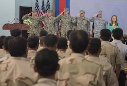 The official party render salutes during the playing of the national anthems during the opening ceremony of Cooperation Afloat Readiness and Training (CARAT) Cambodia 2016. CARAT is a series of annual maritime exercises between the U.S. Navy, U.S. Marine Corps and the armed forces of nine partner nations to include Bangladesh, Brunei, Cambodia, Indonesia, Malaysia, the Philippines, Singapore, Thailand, and Timor-Leste.