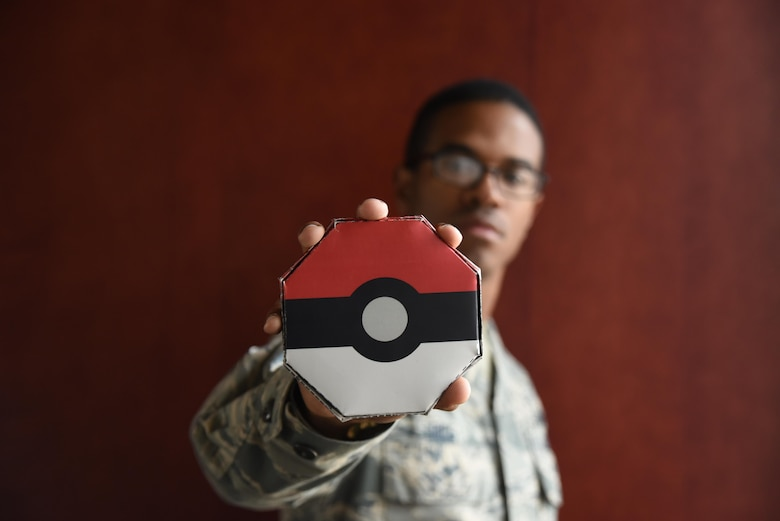 """Airman 1st Class Quintin Rice, 50th Force Support Squadron, shows off his badge case at Schriever Air Force Base, Colorado, Friday, Oct. 28, 2016. Rice earned the title """"Pokemon master"""" after he collected all eight badges during the 50th Space Wing's Chaplain's Office's """"Pokemon challenge."""" (U.S. Air Force photo/Airman William Tracy)"""