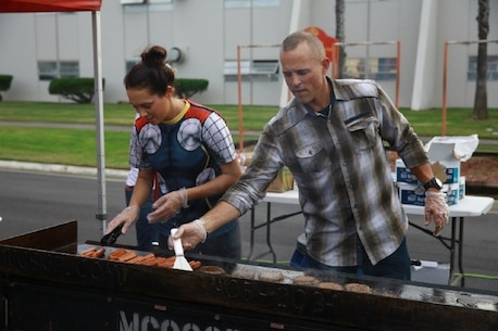 """1st Lt. Malia Haselton, executive officer, Headquarters Company, I Marine Expeditionary Force Headquarters Group, and Master Sgt. Jason Black, operations chief, I MHG, prepare food during """"Trunk or Treat,"""" at Marine Corps Base Camp Pendleton, Calif., Oct. 28, 2016. The event included trick or treating, games, a costume contest, and a free movie showing. (U.S. Marine Corps photo by Pfc. Robert Bliss)"""