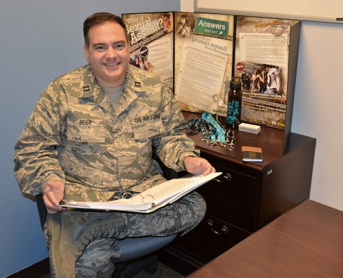 Capt. Lance Beier, the 161st Air Refueling Wing's sexual assault response coordinator, looks over his materials in his office. Beier, a former sailor, soldier and police officer, is devoted to helping people. (U.S. Air National Guard photo by 2nd Lt. Tinashe Machona)