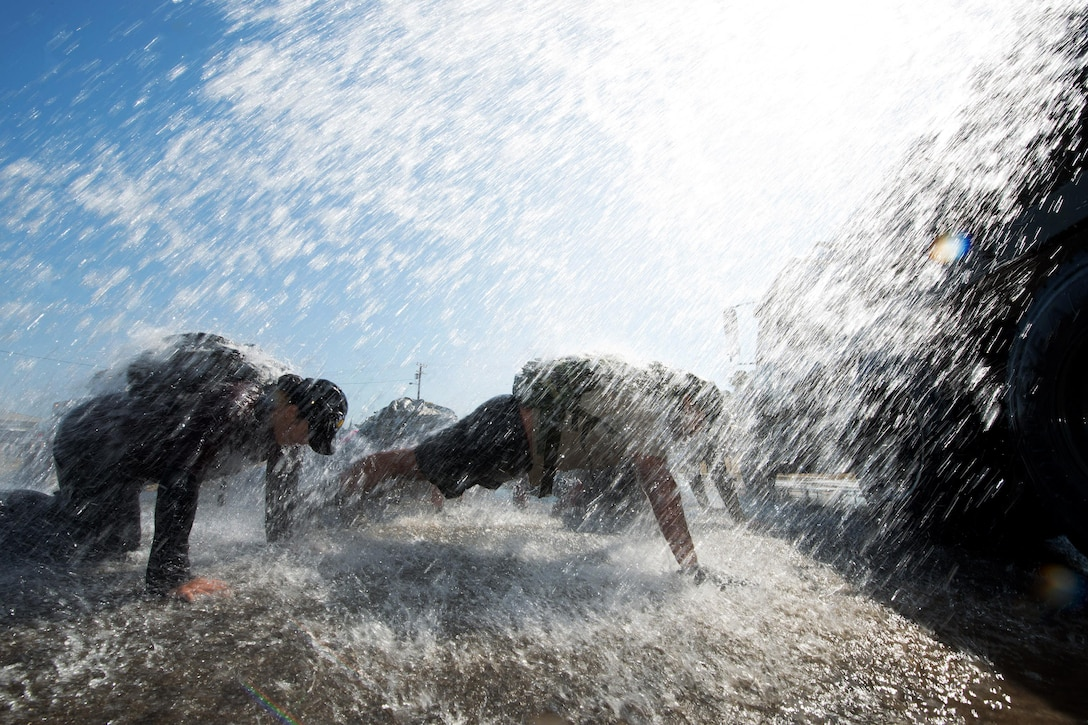 Service members do pushups under rushing water during an event at Travis Air Force Base, Calif., Aug. 26, 2016. The training offers a snapshot of what special operations forces do. Air Force photo by Louis Briscese