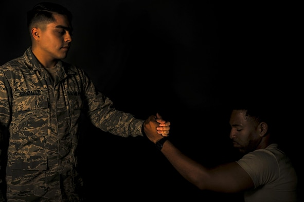 U.S. Air Force Airman Cassidy Gonzales, 23d Medical Operations Squadron mental health technician, grips the hand of Airman Giancarlo Carter, 23d Wing broadcast journalist apprentice, Aug. 31, 2016, at Moody Air Force Base, Ga. Since September is National Suicide Prevention Awareness Month, Air Force leadership takes this time to remind Airmen about the power of wingmanship and emphasize the resources available to combat hard times. (U.S. Air Force photo by Airman 1st Class Daniel Snider)