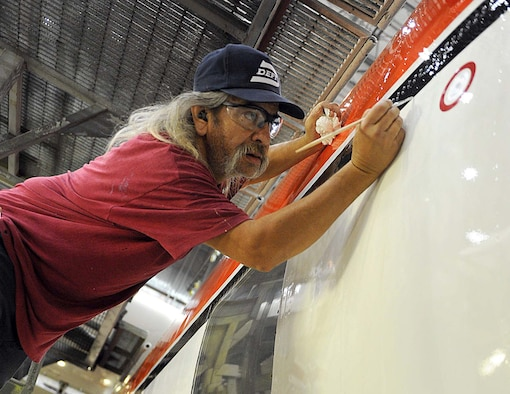 Sam Vigil, 402nd Aircraft Maintenance Support Squadron aircraft painter, touches up paint on a Coast Guard C-130H recently modified for transfer to the U.S. Forest Service. (U.S. Air Force photo by Tommie Horton)