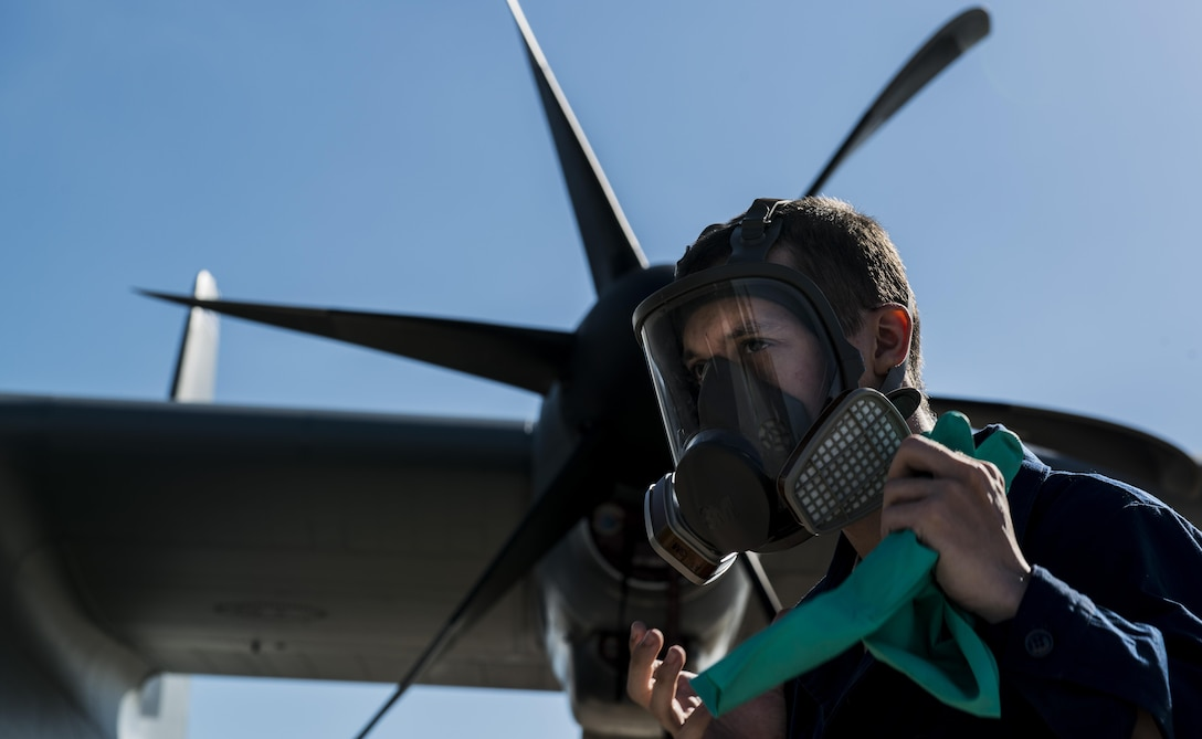Airman 1st Class Christopher Jones, 786th Civil Engineer Squadron pest management specialist, dons gloves before spraying Callington Pre-Spray in a C-130J Super Hercules to prevent the spread of the zika virus Aug. 29, 2016 at Ramstein Air Base, Germany. Once the plane has been sprayed, it is closed for 30 minutes to allow the pre-spray to settle, then opened to air out for an additional 30 minutes. (U.S. Air Force photo/Senior Airman Tryphena Mayhugh)