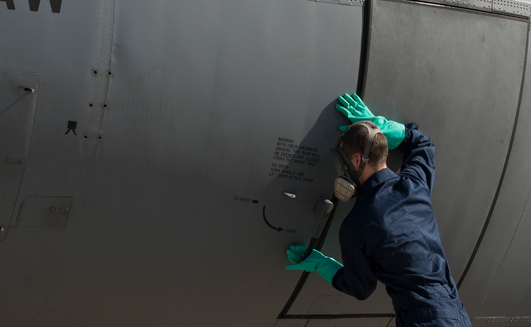 Airman 1st Class Christopher Jones, 786th Civil Engineer Squadron pest management specialist, closes the door of a C-130J Super Hercules after spraying the inside with Callington Pre-Spray to prevent the spread of the zika virus Aug. 29, 2016 at Ramstein Air Base, Germany. Jones closed the aircraft to allow the pre-spray to settle for 30 minutes. (U.S. Air Force photo/Senior Airman Tryphena Mayhugh)