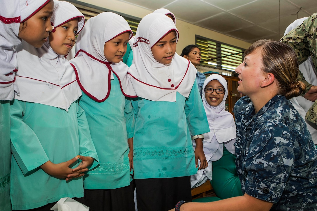 Navy Petty Officer 3rd Class Emily Cates talks with students from a primary school