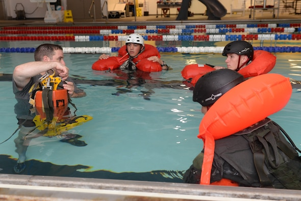 Airmen from the 54th Helicopter Squadron listen to instructions from Staff Sgt. Anthony Barrette, a survival, evasion, resistance and escape specialist assigned to the 5th Operations Support Squadron, during water egress training at the McAdoo Fitness Center at Minot Air Force Base, N.D., Aug. 31, 2016. SERE specialists explained procedures to escape a crashed helicopter and how to properly use common rescue devices used by all branches of the armed forces. (U.S. Air Force photo/Airman 1st Class Jessica Weissman
