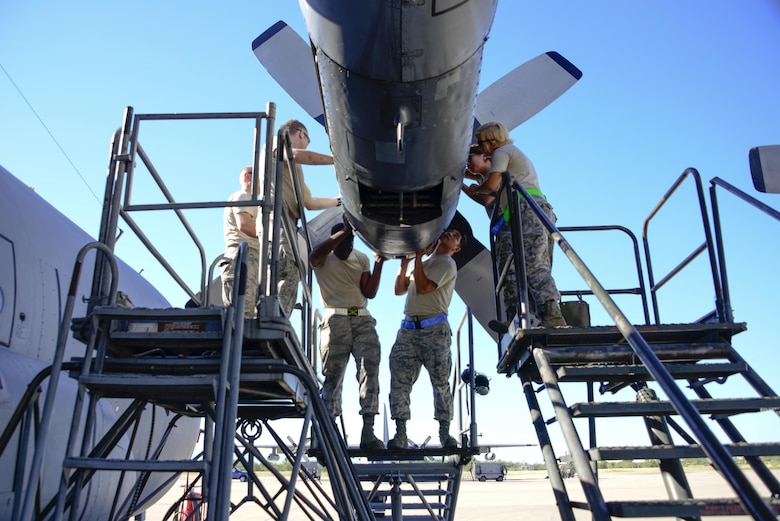 U.S. Airmen from the 755th Aircraft Maintenance Squadron install a new chin scoop on an EC-130H Compass Call at Davis-Monthan Air Force Base, Ariz., Aug. 31, 2016. The chin scoop aids in getting air to the engines compressor. (U.S. Air Force photo by Senior Airman Betty R. Chevalier)