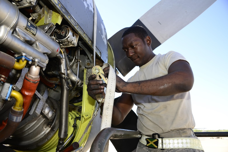 U.S. Air Force Senior Airman George Thompson, 755th Aircraft Maintenance Squadron aerospace propulsion journeyman, tightens a ratchet strap around the engine of an EC-130H Compass Call at Davis-Monthan Air Force Base, Ariz., Aug. 31, 2016. Thompson used the ratchet strap to hold a chin scoop against the base of the aircrafts engine while he and additional members of the 755th AMXS fastened it in place. (U.S. Air Force photo by Senior Airman Betty R. Chevalier)